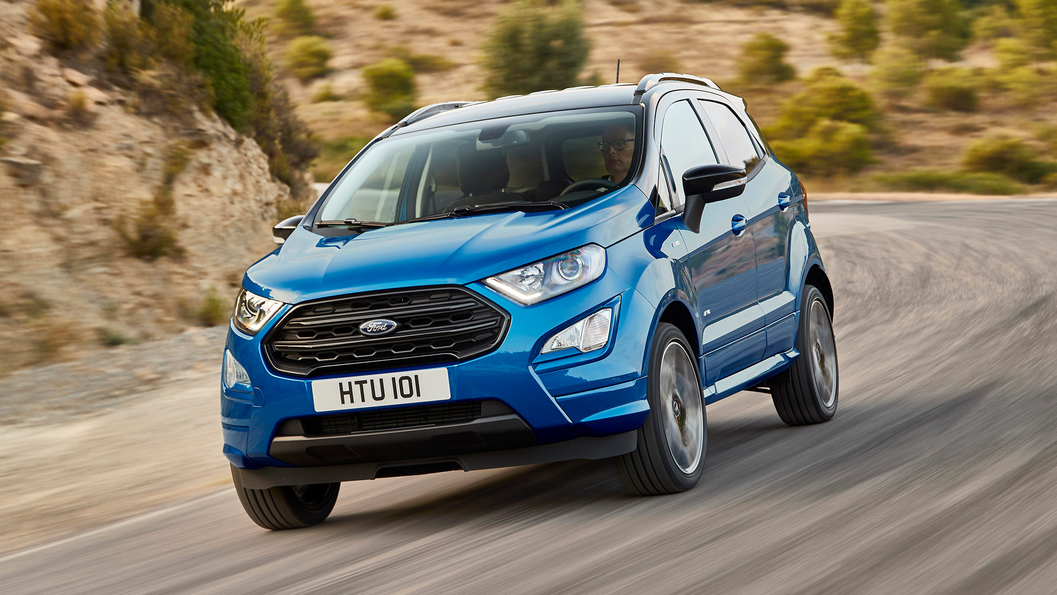Blue EcoSport driving around corner