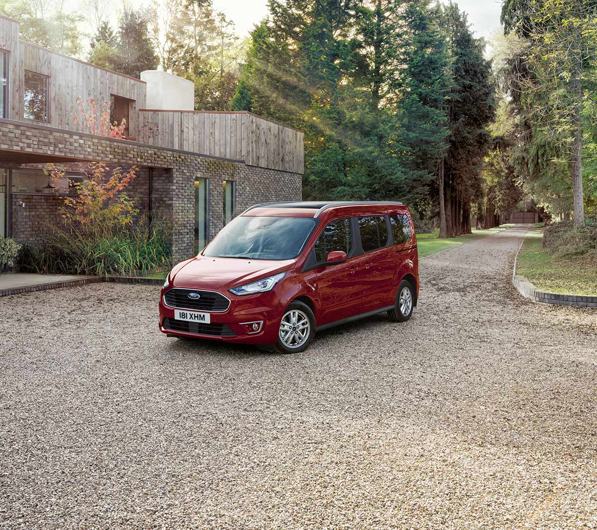 New Red Ford Tourneo Connect parked next to modern country house